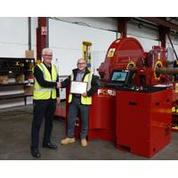 David Neill of TAM International (left) receives a plaque from George Hendry, business development manager for Forum AMC, recognising the purchase of the 350th RT torque machine. (Photo: TAM)
