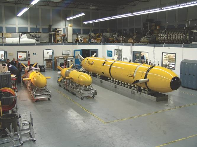 International Submarine Engineering (ISE) and the Canadian Department of National Defense developed Theseus (pictured in the ISE Shop with Explorer AUV and the prototype AUV ARCS) to lay fiber-optic cable under the Arctic ice pack. The vehicle was deployed to the Arctic in 1995 and 1996. In 1996, several 220 km cables were laid in 600 meter water depths under a 2.5 meter thick ice pack, establishing an AUV endurance record of over 60 hours – all under ice. (Photo: ISE)